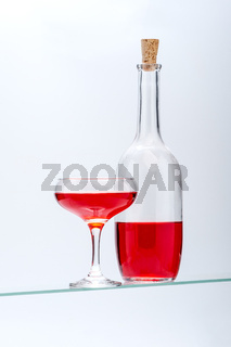 Wine glass and bottle with red alcoholic drink on a light gray background.