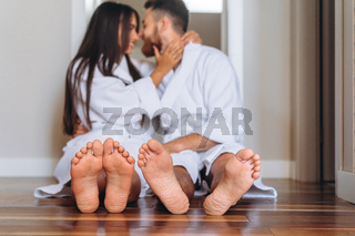 Barefoot woman and man sitting on floor at home