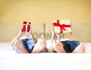 Sweet family in bed. Three sisters, close up on gift box