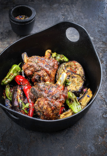 Traditional barbecue leg of lamb with eggplant and chili as top view in a modern style Japanese cast-iron roasting dish