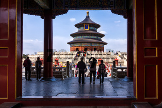 Tourists taking pictures in front of Temple of Heaven, view through open gate. Beijing