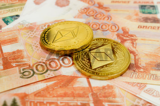 Close-up of Ethereum coins on 5000 Russian rubles banknote. Crypto currency ETC.