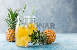Fresh pineapple juice and ripe pineapple on grey background