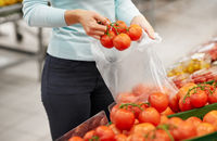 woman with bag buying tomatoes at grocery store