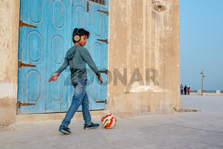 Boy kicking ball while passing in front of the camera