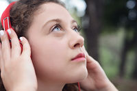 Portrait of young beautiful woman with red headphones listening music