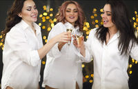 Smiling women with glasses of champagne over lights background. Party, drinks, ho