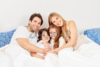 Glückliche Eltern und zwei Kinder beim Kuscheln