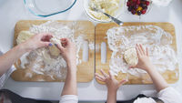 Mom and daughter hands sprinkles flour on the board for preparing pancakes