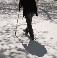 One person with crutch walking on concrete with tree shadows. Retirement