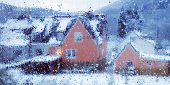 view through a window with condensation water and rain drops to a house in winter, Witten, Germany