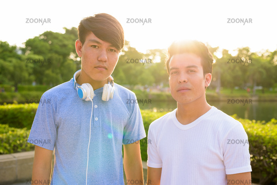 Photo Young Asian man and young Asian teenage boy at the park ...