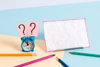 Mini small size alarm clock beside stationary placed tilted. Notepaper on the edge of empty plain multi colours table backdrop. Artistic way of arranging flat lays photography