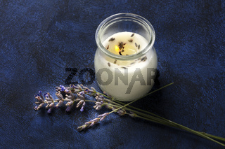 A burning lavender scented candle on a dark background with copy space. Zero waste Christmas concept, a handmade New Year gift in a recycled glass jar