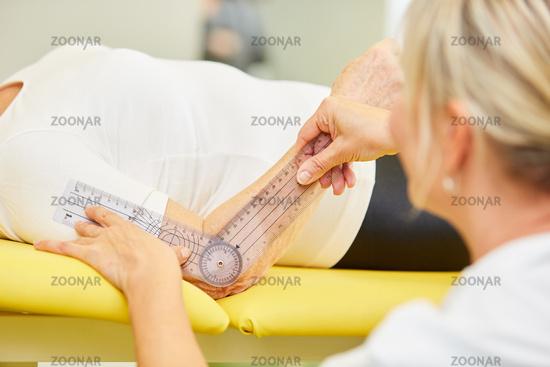 Ärztin oder Physiotherapeutin mit einem Goniometer
