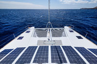 Luxury solar powered catamaran, fully sustainable and powered by solar energy, charging batteries aboard a sailboat, vessel in ocean waters, nobody. Photovoltaic panels renewable eco energy concept