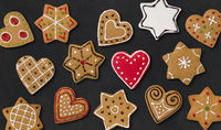 Several gingerbread hearts and stars on a dark background