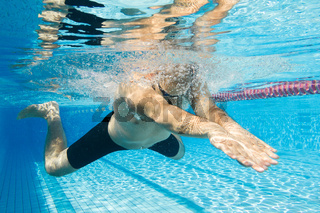 Young male athlete swimming breaststroke under water view.