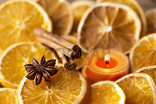 Orange slices, spices and scented candle as Christmas decoration