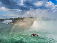 The boat surrounded by mist under Niagara waterfalls passing under the rainbow.