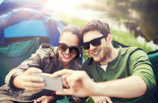 couple of travelers taking selfie by smartphone