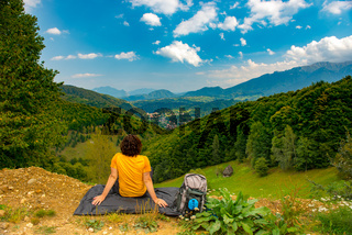 Young mountain hiker sitting on a waterproof nylon blanket in a beautiful mountain landscape and enjoying the view. Hiker concept for summer designs.