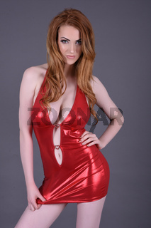 Ashley Foxx, sexy vollbusige Rothaarige, in einem engen rot glanzendem Kleid