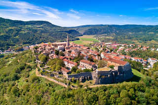 Buzet. Hill town of Buzet surrounded by stone walls in green landscape aerial view.