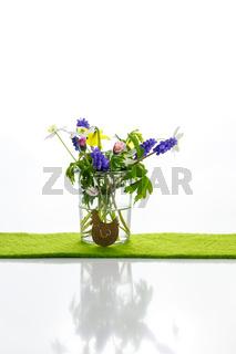 Kleine Blüten in einer Vase mit einem kleinen Huhn. Ostern. Dezent.