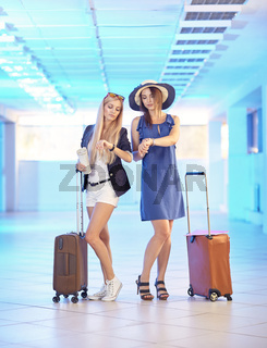 Two young women  with suitcases in the airport