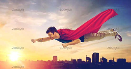 man in superhero cape flying over sunset in city