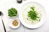 Cream soup with arugula and pine nuts in a white bowl