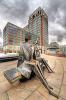 bronze sculpture of two people sitting on a bench at canary wharf