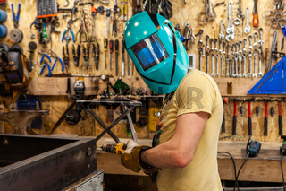 Metalworker wears protective mask