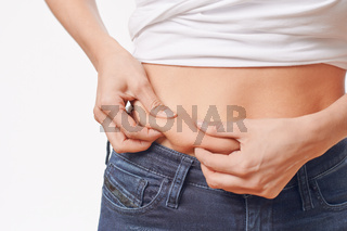 Junge Frau prüft ihr Bauchfett