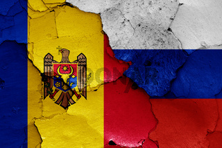 flags of Moldova and Russia painted on cracked wall