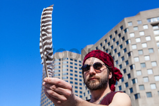 Boho man holds eagle feather in city