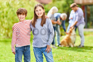 Glückliche Geschwister auf dem Rasen im Garten