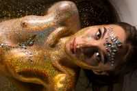 Woman in gold glitter in bath high angle shot