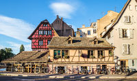 Several bicycles are located along the old houses in Strasbourg, France