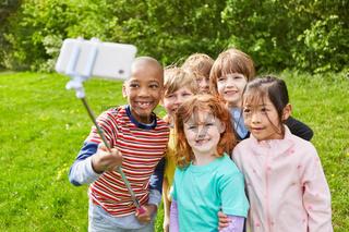 Gruppe Kinder macht Selfie mit Selfie Stick