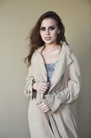 Beautiful young fashion model wearing a trench coat