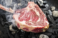 Traditional raw dry aged wagyu tomahawk steak on hot burning charcoal with smoke as closeup on a barbecue fire