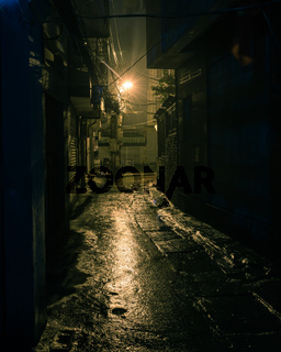 Filtered image empty and dangerous looking urban back-alley at night time in suburbs Hanoi