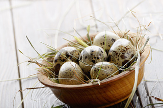 Fresh organic quail eggs in wooden bowl on rustic kitchen table. Space for text