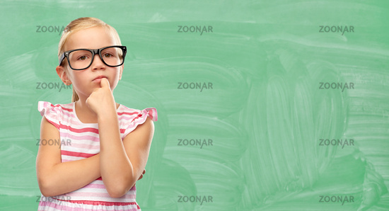 cute little girl in glasses thinking at school