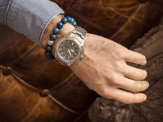 Crop shot of man showing wrist watch over sofa