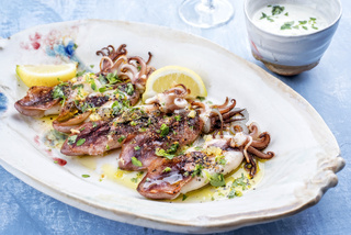 Traditional barbecue Greek calamari with herb and lemon as top view on a plate