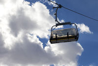 Chair-lift and sunlit sky with clouds at evening