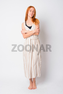 Full body shot of young beautiful redhead woman with arms crossed